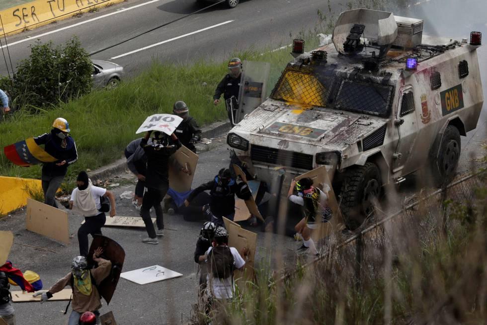 Un vehículo blindado atropella a un grupo de manifestantes durante una protesta contra el Gobierno de Nicolás Maduro, este martes en Caracas.