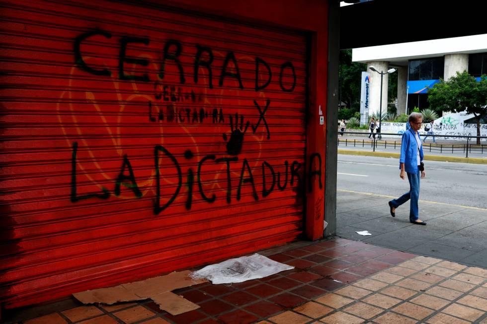 Una mujer pasa junto a un comercio cerrado por la huelga, ayer en Caracas.