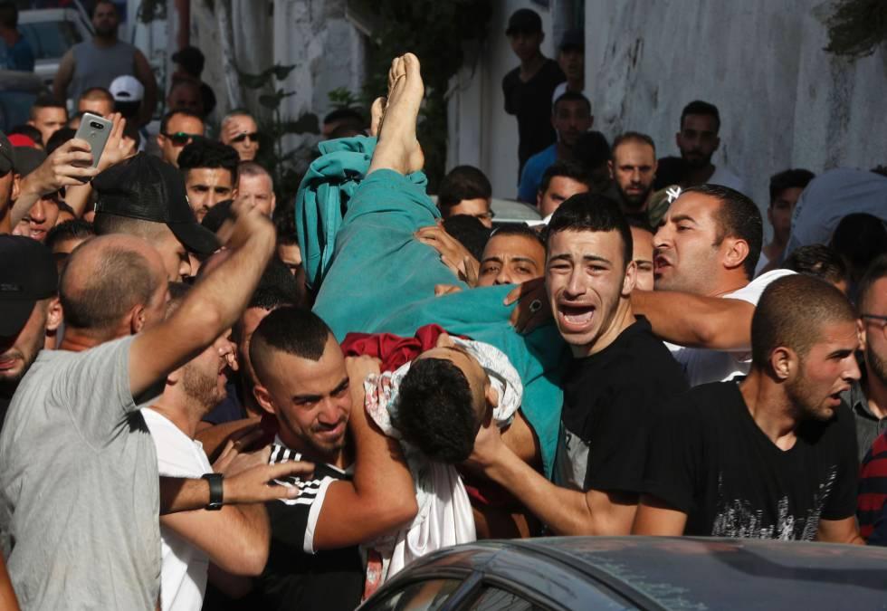 Varios hombres llevan el cuerpo de un hombre muerto por un disparo durante los disturbios en Jerusalén Este.