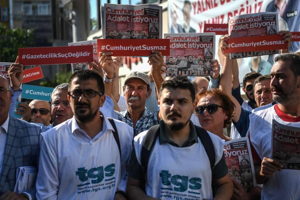 Compañeros de los periodistas detenidos y manifestantes sostienen copias del diario 'Cumhuriyet' el inicio del juicio contra 19 de sus empleados y directivos este lunes en Estambul.