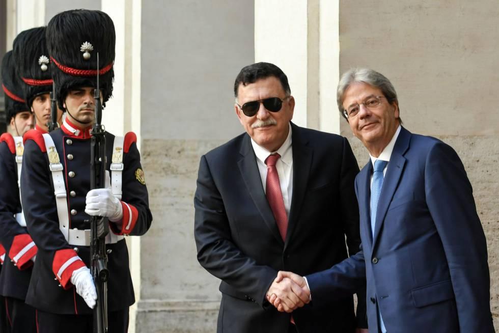 Paolo Gentiloni (derecha) estrecha la mano del primer ministro libio, Fayez al-Sarraj.