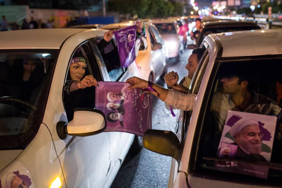 Partidarios de Rohani reparten carteles durante la campaña electoral.
