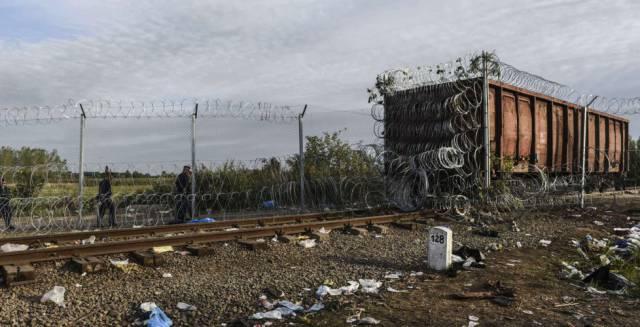 La policía húngara camina al lado de un vagón de ferrocarril cubierto de alambre en la frontera de Hungría con Serbia.