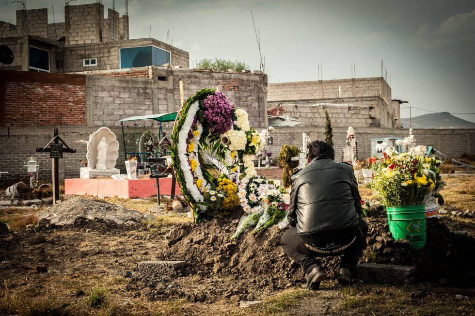 Un hombre visita la tumba de una mujer asesinada en Ecatepec.