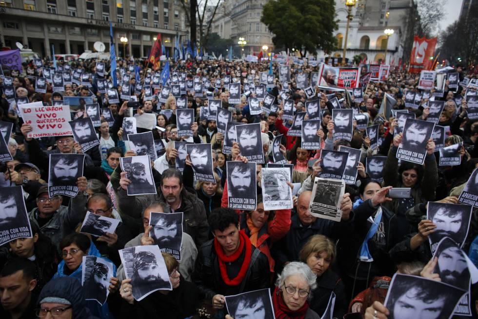 Los asistentes a la marcha exhiben el rostro del joven desaparecido.