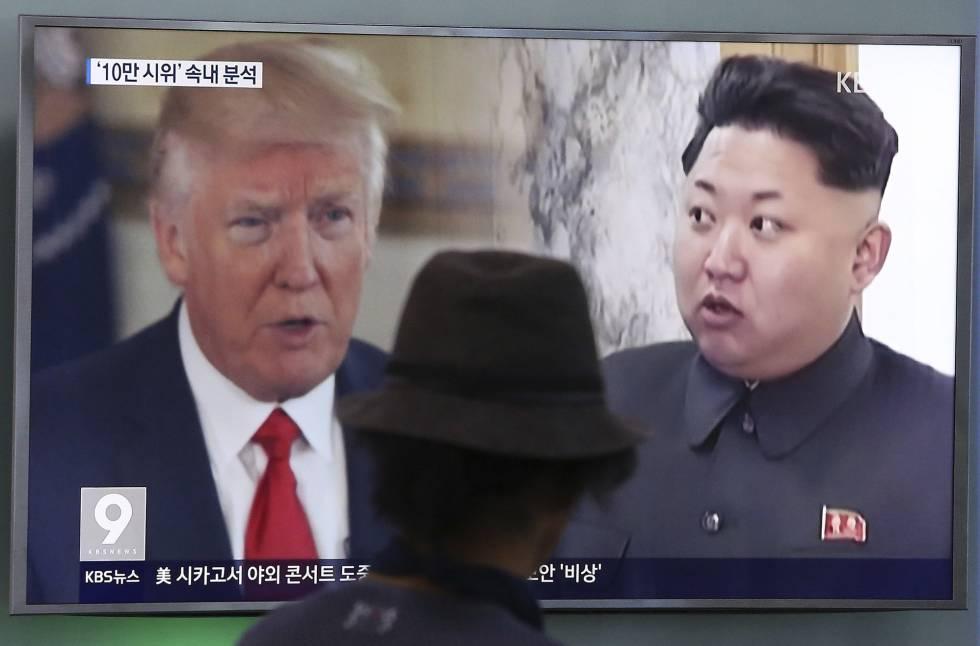 Un hombre mira una televisión en la que aparecen Kim Jong Un y Donald Trump.