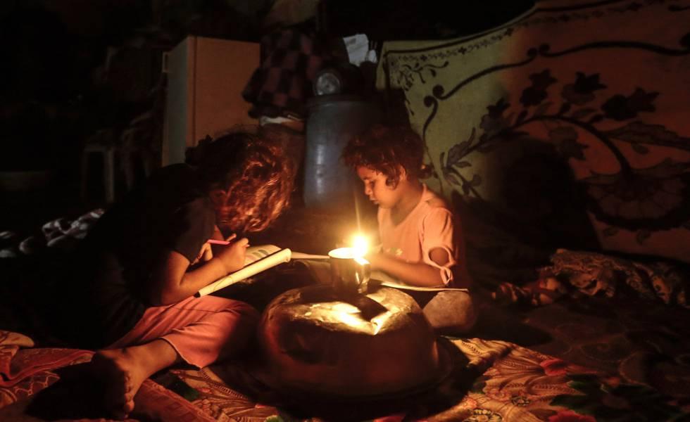 Dos niños palestinos hacen los deberes durante un apagón en Gaza.