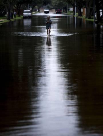 Una mujer recorre una calle en Houston inundada por Harvey.