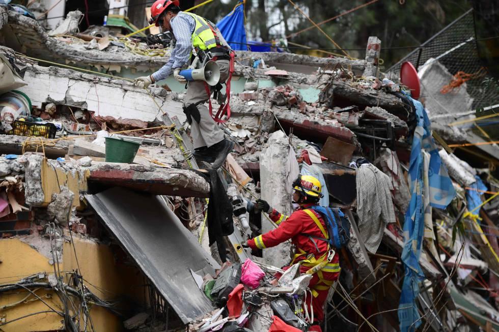 Dos rescatistas trabajan en un derrumbre de la Ciudad de México.