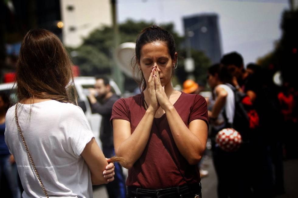Una mujer reza mientras espera que una persona sea rescatada.