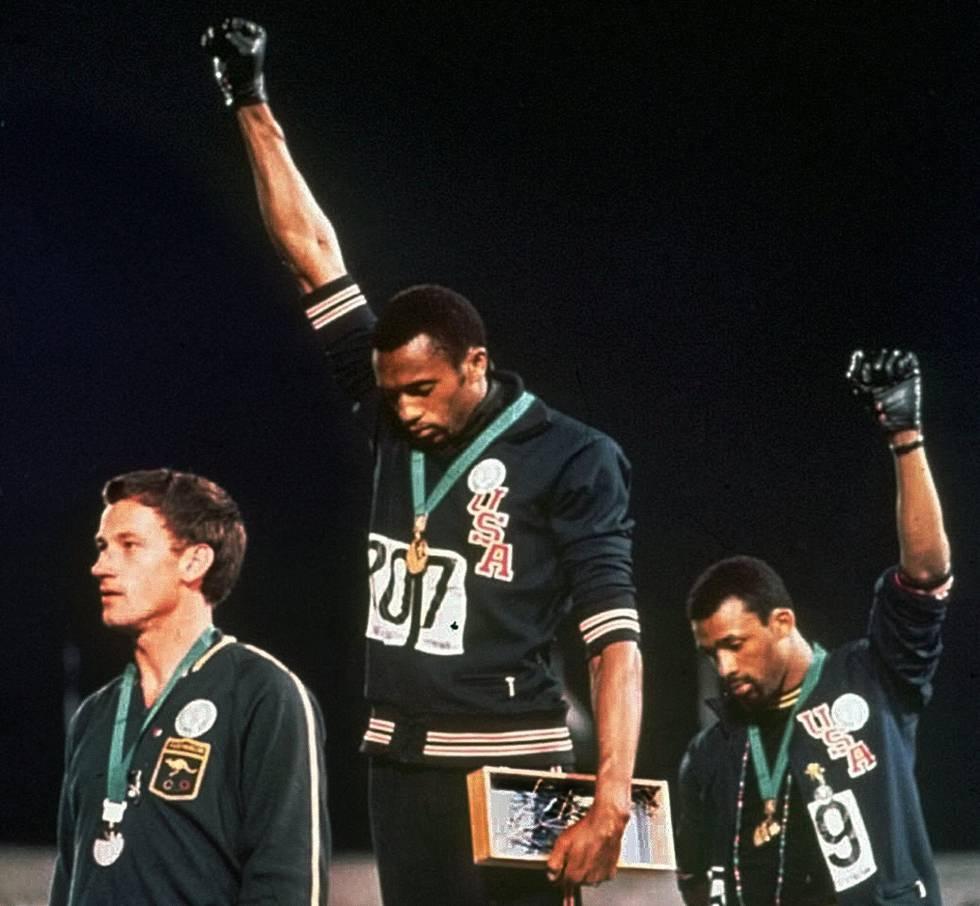 Los atletas Tommie Smith, en el centro, y John Carlos, alzan el puño en los Juegos Olímpicos de México de 1968