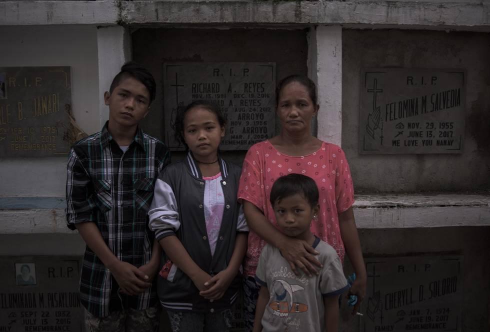 Teresita Yabut y sus hijos ante el nicho de su esposo.