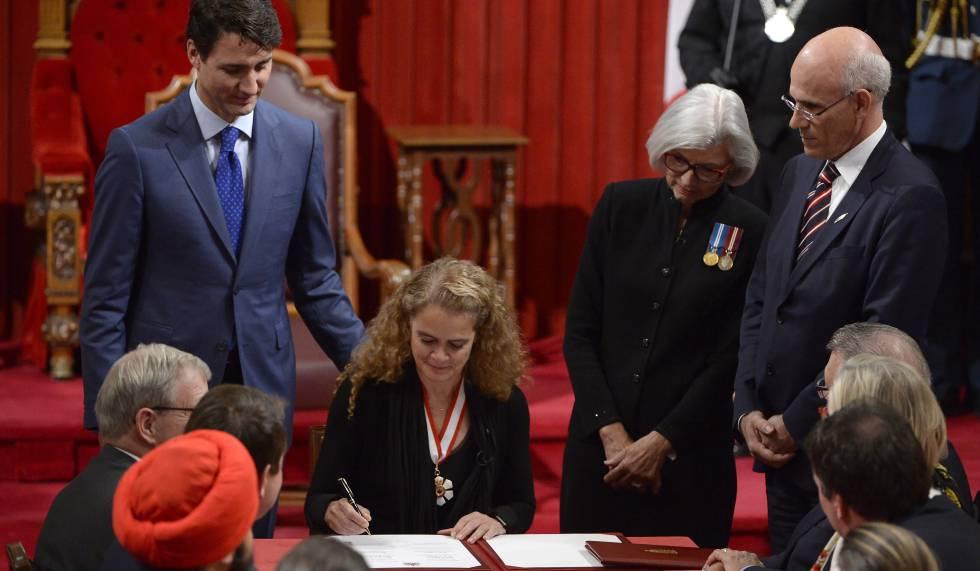 Julie Payette firma su cargo ante la mirada del primer ministro, Justin Trudeau.