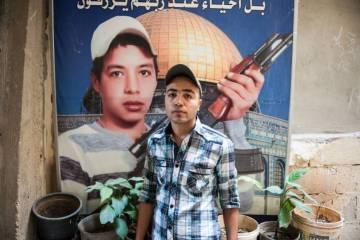 El palestino Mohamed Abu Shaqra, de 24 años, posa delante del retrato de su hermano Imad delante de su casa, al sur del Líbano.