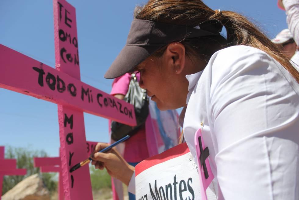 Susana Montes pinta una dedicatoria en la cruz que recuerda a su hija asesinada.