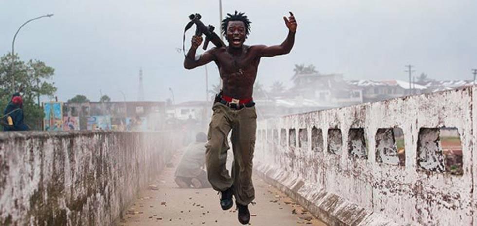 Joseph Duo, cuando era niño soldado, salta tras haber descargado su lanzagranadas, en plena guerra civil en Liberia.