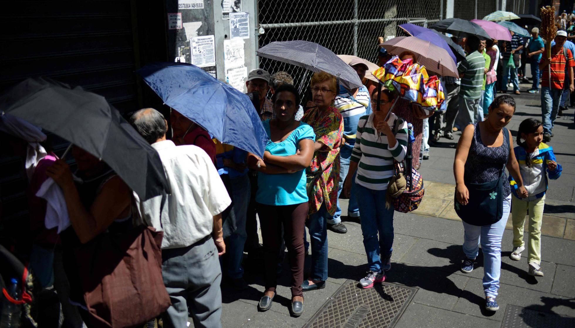 Un grupo de personas hace cola a las puertas de un supermercado en Caracas. FEDERICO PARRA AFP