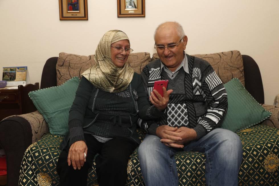 Ana Lobato junto a su marido Abdalazem Alfaraj Al Shoeib, viendo las fotos de sus hijos en el télefono móvil, este lunes en Madrid.