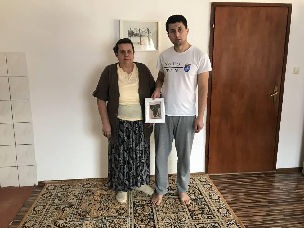 Sead Halilovic, junto a su madre Sefika, muestra la foto de su padre Hadid, asesinado en la matanza de Srebrenica.