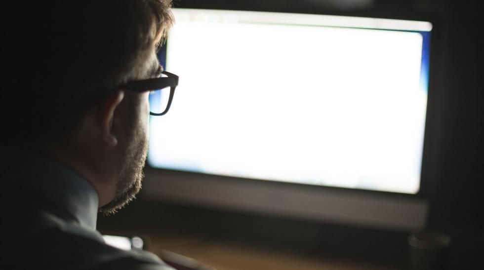 Un hombre mira la pantalla de su ordenador.