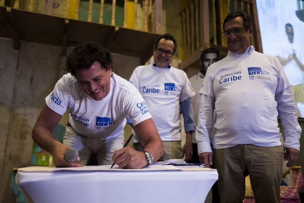 El cantante Carlos Vives firma el compromiso de inversión de Casa Grande Caribe, junto a Marco Schwartz, director de 'El heraldo de Barranquilla', y Adolfo Meisel, codirector del Banco de la República.