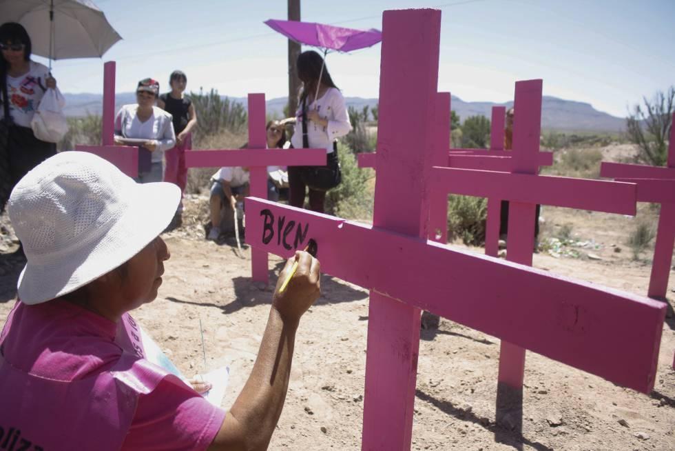 Una madre pinta en una cruz el nombre de una víctima de feminicidio.