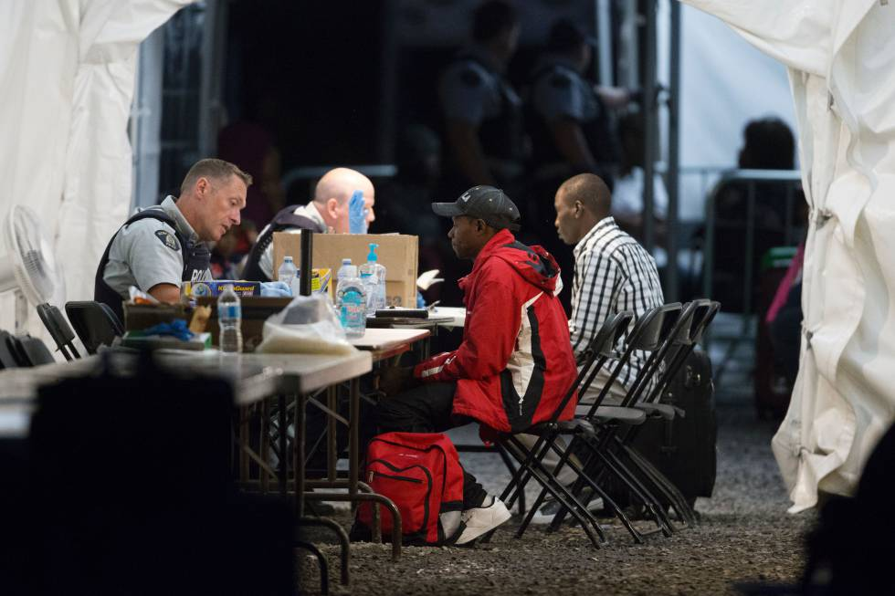 Refugiados arrestados por la policía canadiense tras haber cruzado la frontera con Estados Unidos, cerca de Hemmingford, Quebec, el pasado agosto.
