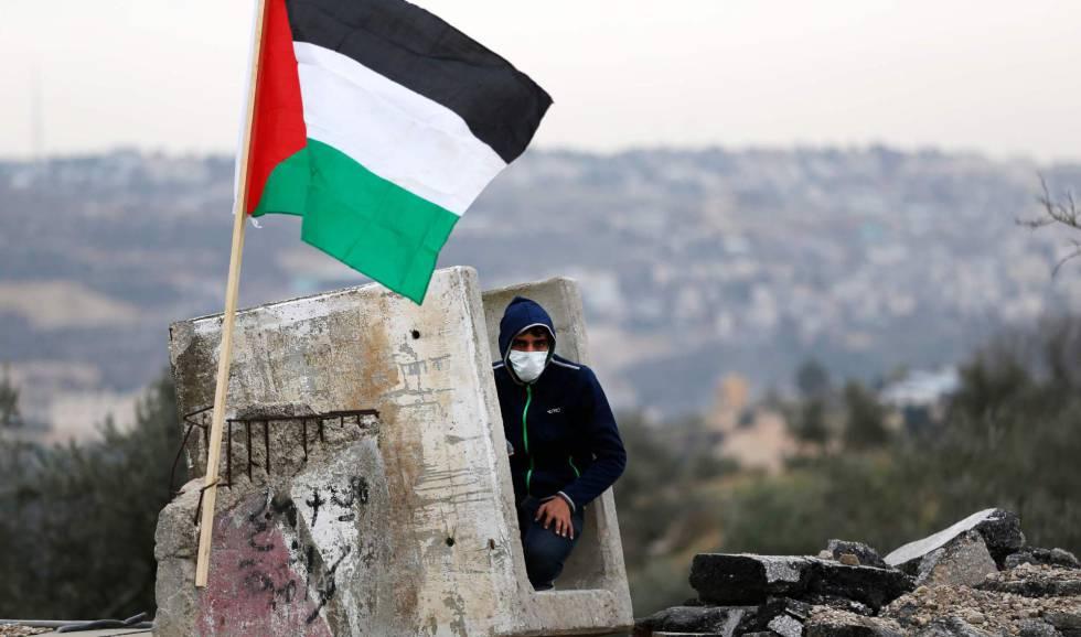 Manifestante palestino se refugia em um bloco de concreto.