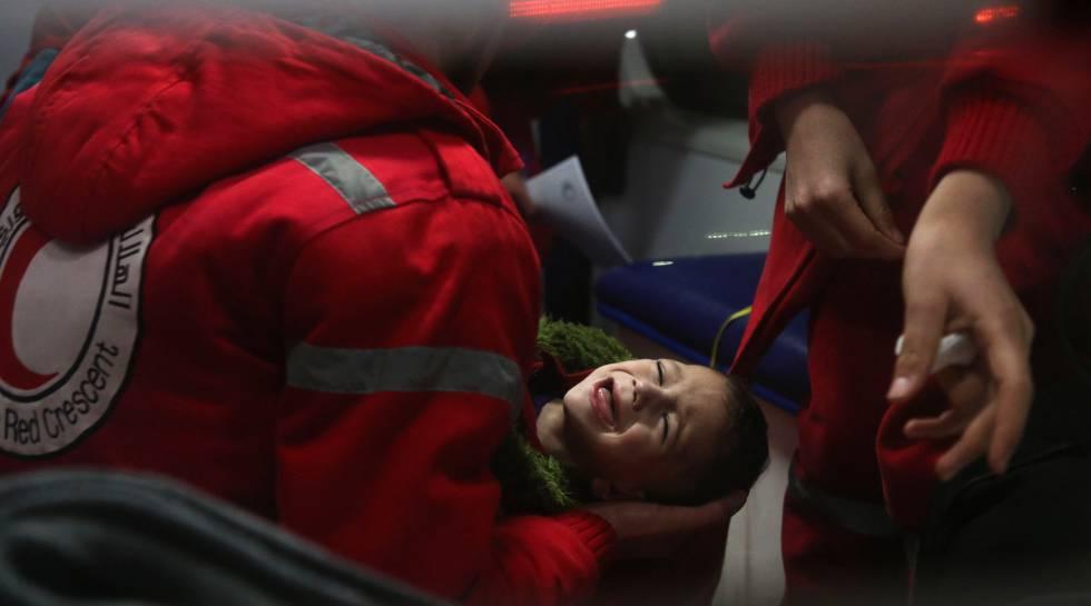 Personal de Media Luna Roja atiende a un menor durante la operación de evacuación de la localidad siria de Guta.