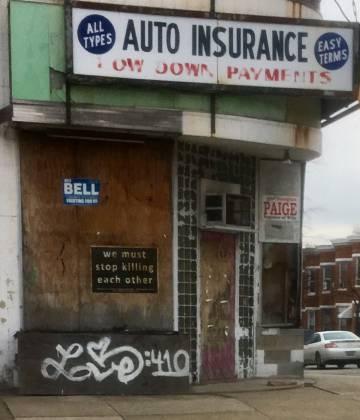 """""""Tenemos que dejar de matarnos entre nosotros"""", reza un cartel pegado a una placa de madera de un comercio tapiado en West Baltimore"""