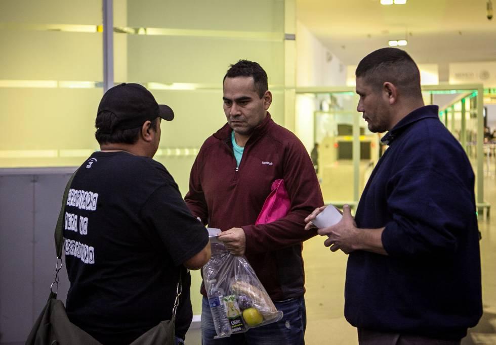 Felipe (d) y otro compañero reciben a un deportado en el aeropuerto.