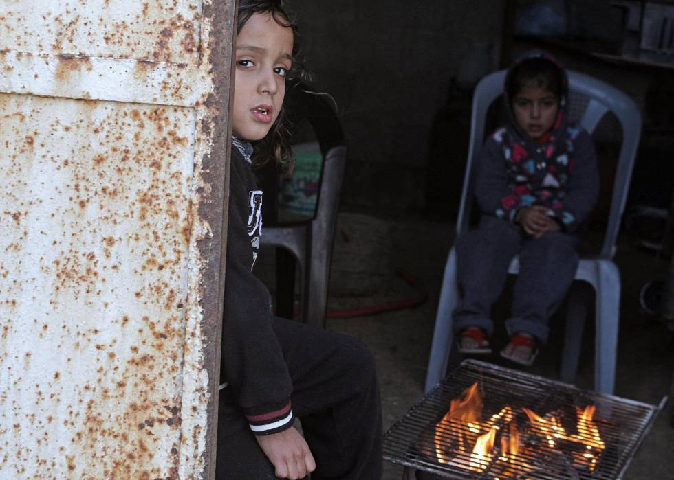 Niños palestinos se calientan con un brasero en el campamento de refugiados de Al Shateaa, en Gaza.