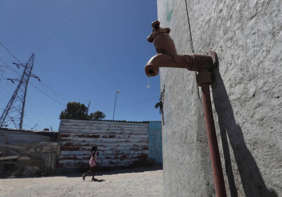 Una joven camina cerca del grifo comunal en el barrio Khayelitsha en Ciudad del Cabo.