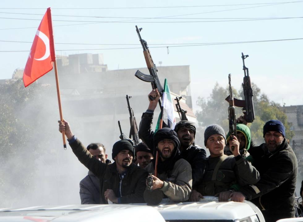 Miembros del Ejército Libre Sirio (ELS) circulan junto a tropas turcas en la ciudad siria de Azez, cerca de la frontera con Turquía, este viernes. Fuerzas del ELS han atacado posiciones de las YPG en Afrin dentro de la ofensiva turca contra el cantón kurdo-sirio.