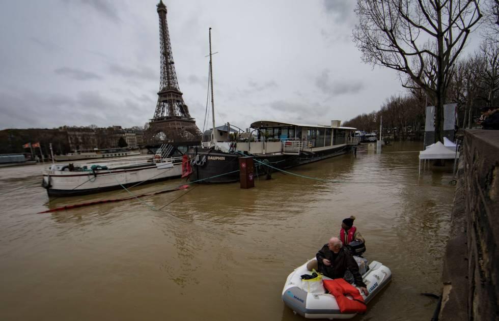 Un hombre transporta a un pasajero en un bote en el desbordado río Sena, París (Francia) este 25 de enero de 2018.