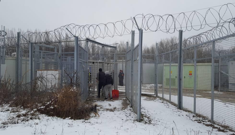Haj y Musafir en uno de los controles de la frontera de Serbia con Hungría, tras la valla, los contenedores que las autoridades húngaras han convertido en viviendas.