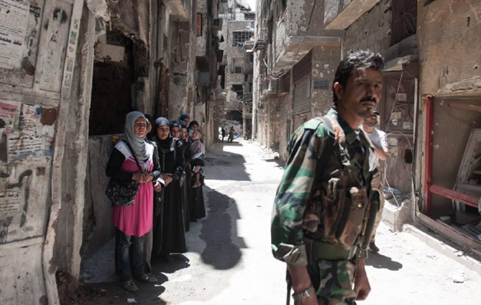 Refugiados palestinos esperan el reparto de alimentos en el campo de Yarmuk, al sur de Damasco (Siria), durante la guerra siria en 2014.