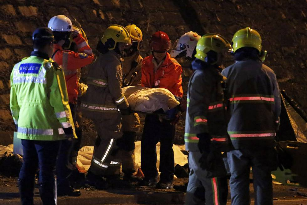 Los equipos de rescate apartan un cuerpo tras el accidente de autobús este sábado en Hong Kong.