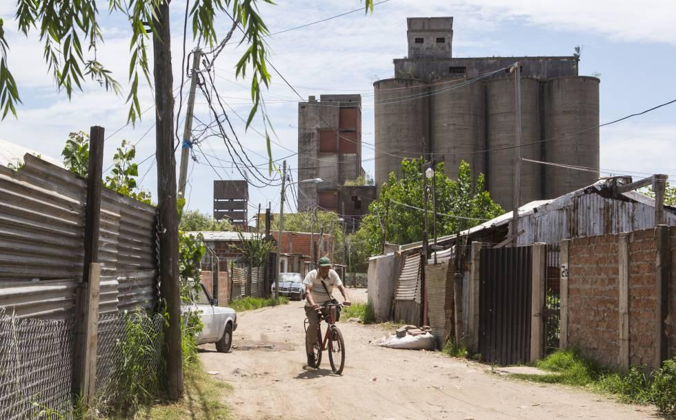 Un hombre circula en bicicleta por una calle de Villa Inflamable.