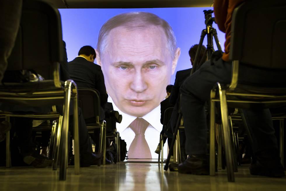 Varios peridostas siguen el discurso de Putin en Moscú.