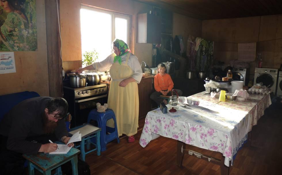 Ksenia e Ulian Murashov com um de seus filhos na cozinha da sua casa.