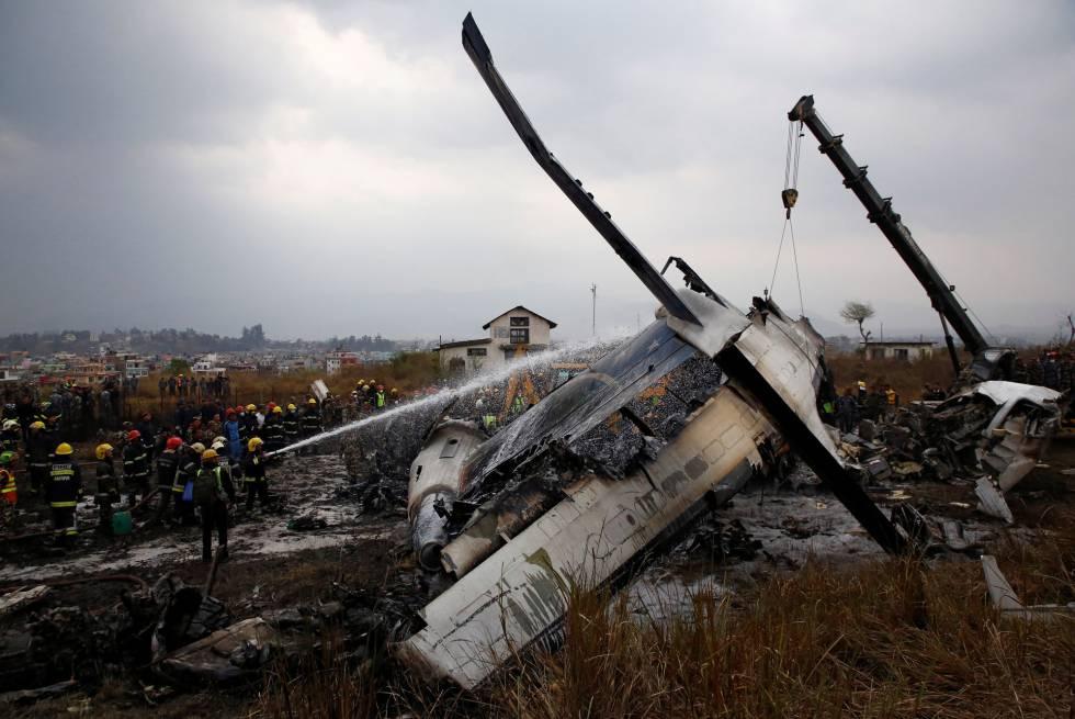 Los bomberos apagan las llamas del avión accidentado en Nepal procedente de Bangladés.