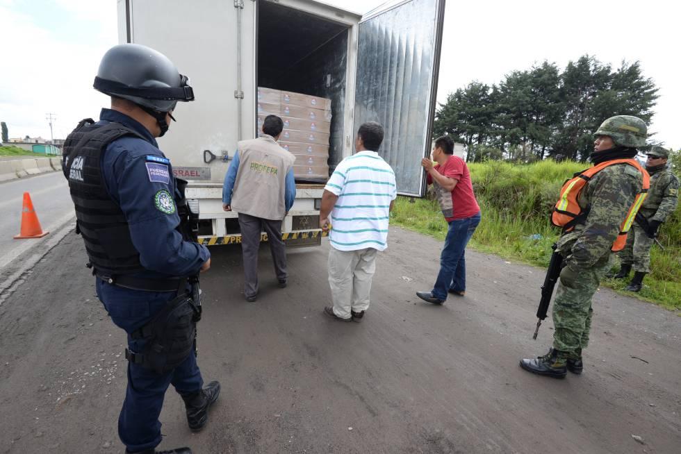 Policías y militares realizan una inspección a camiones de carga en el Estado de México.