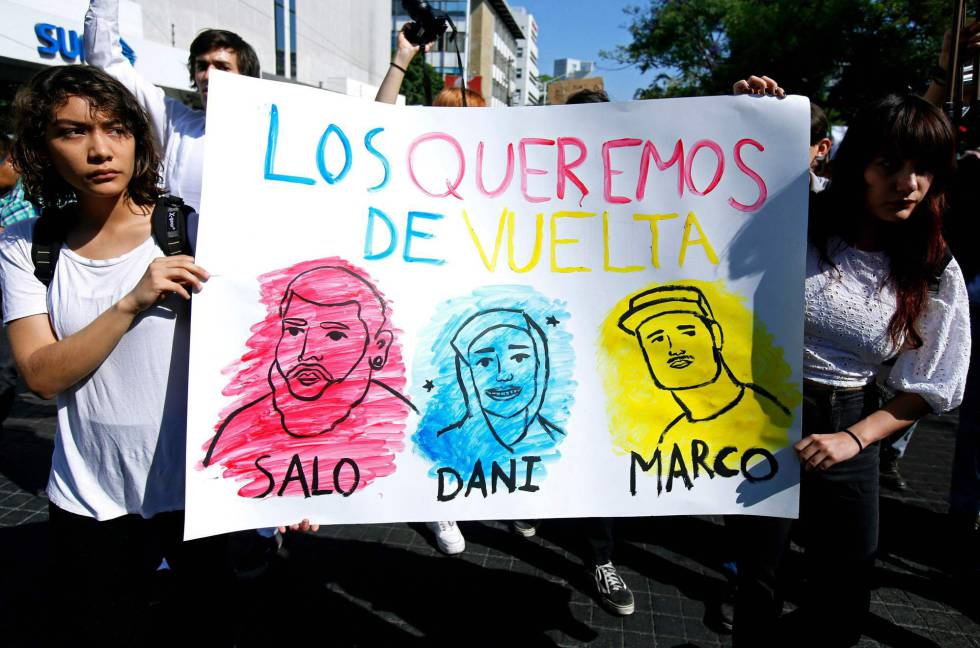 Dos jóvenes marchan en solidaridad con sus compañeros desaparecidos.