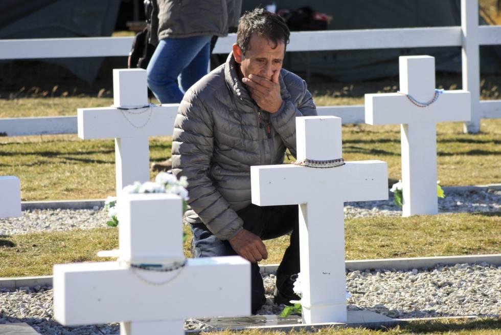 El familiar de un soldado argentino identificado en Malvinas llora ante su tumba en el cementerio de Darwin.