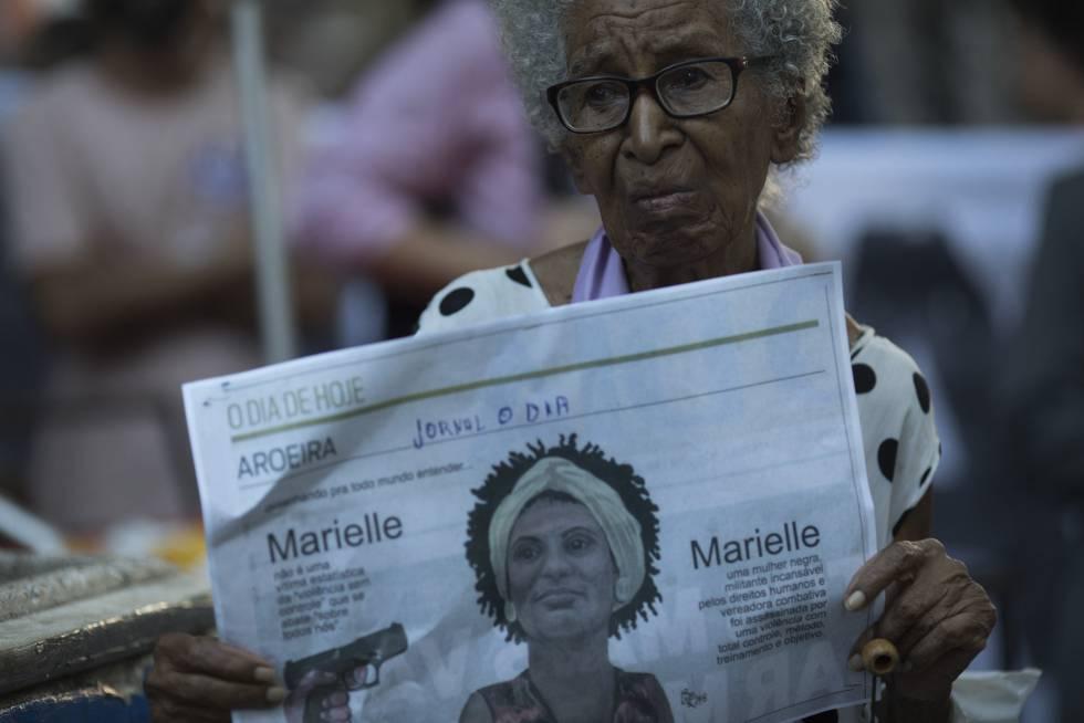 Una mujer muestra un periódico con el rostro de Marielle Franco.