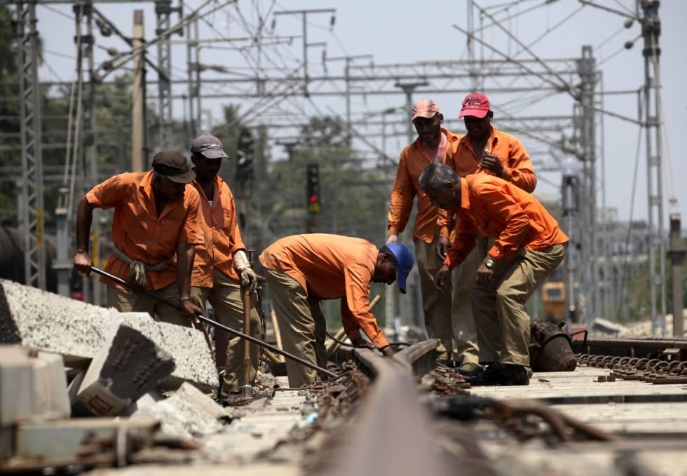 Un grupo de trabajadores del ferrocarril repara un tramo de vía en Ghatkopar, Mumbai (India).