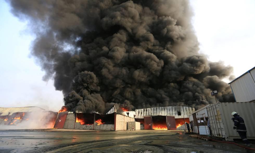 Bomberos, este sábado tratando de apagar el incendio en el puerto de Al Hudayda (Yemen).