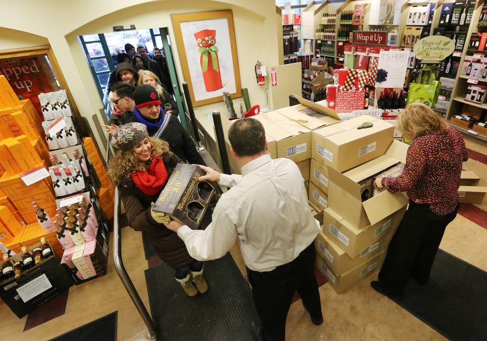 Un grupo de clientes compra un surtido de cajas de cerveza Westvleteren.