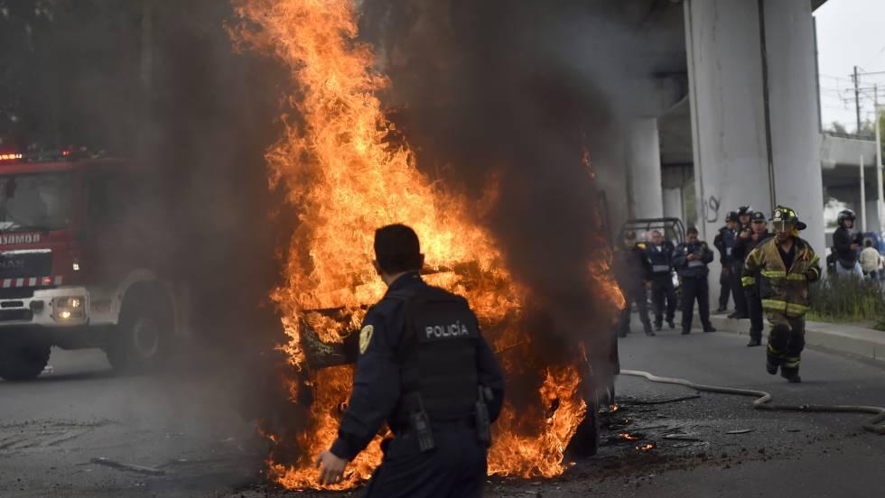 Un policía frente a los microbuses incendiados el pasado 20 de julio en Tláhuac tras el operativo militar contra El Ojos.